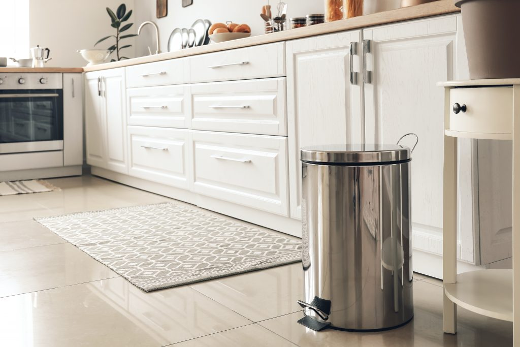 apartment kitchen with a lidded trashcan